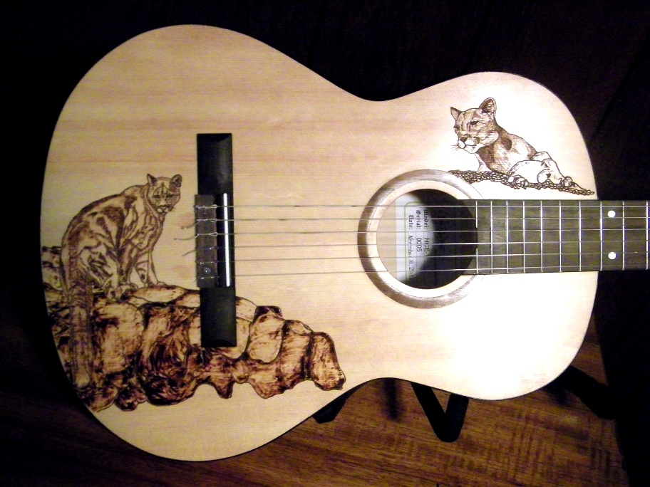 The Pyrographic Wood Burned Artwork On Body Of This Guitar Depicts Two Panthers One Lower Bout Sitting A Stone Outcropping And Other